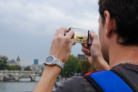 ile de la cite: Tourist taking photo of Île de la Cité and bridge with  smart phone