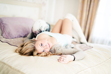 Attractive young woman is holding a dog while laying on a bed photo