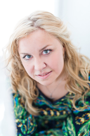 cortinas blancas: Mujer atractiva joven en contra de las cortinas blancas