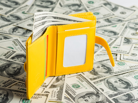 caretaking: yellow Wallet Resting Upon Many United States One Hundred Dollar Notes.  Stock Photo