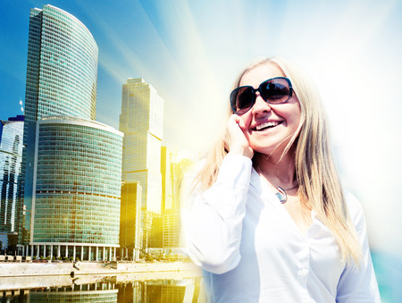 mackintosh: Young businesswoman with mobile phone. On modern city background.  Stock Photo
