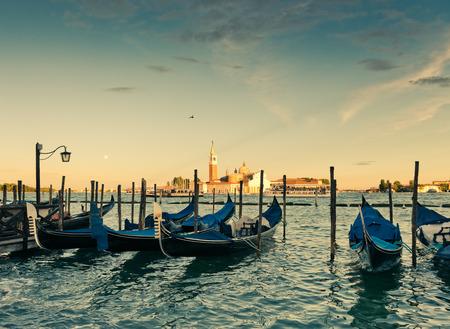 Gondolas moored by Saint Mark square with San Giorgio di Maggiore church in the background - Venice, Italy photo