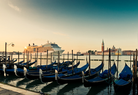 Gondolas on the background of the huge cruise ship in Venices Grand Canal. photo