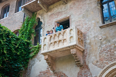 VERONA, ITALY - JULY 11 2014: balcony of Juliet with turists in Verona. It is the suspected parents home of Juliet, the character in the famous tragedy of Shakespeare.