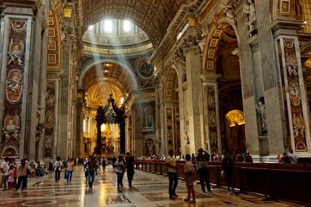 people in church: VATICAN CITY, VATICAN - JULY 15 2014: People at the interior of the Saint Peter Cathedral in Vatican. Saint Peters Basilica has the largest interior of any Christian church in the world.