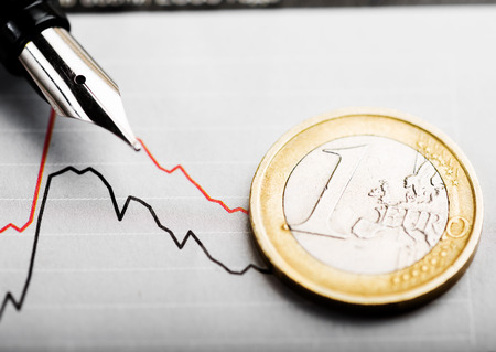One euro coin on fluctuating graph. Rate of euro (shallow DOF) photo