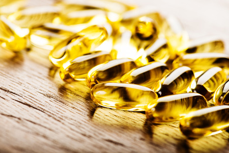 Fish oil omega 3 gel capsules isolated on wooden background photo