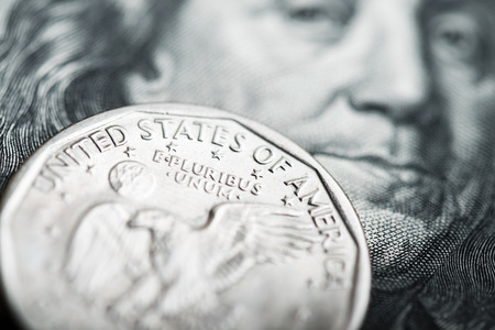 Portrait of Benjamin Franklin from one hundred dollars banknote and one dollar coin photo
