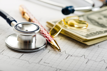 Dollars, stethoscope, pills and cardiogram. Costs for the medical insurance. photo