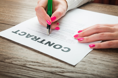 Businesswomans hand with pen signing a contract. photo