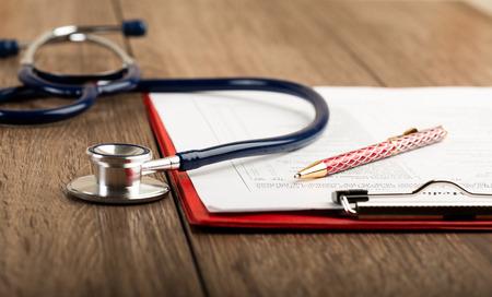 historia clinica: historial médico con el estetoscopio y la pluma en el escritorio de madera Foto de archivo
