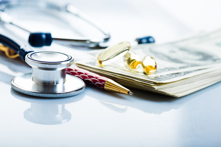 Dollars, stethoscope, pills. Costs for the medical insurance.