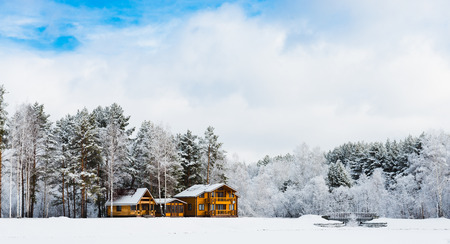 Wooden houses in a nature area covered with freshly fallen snow. photo