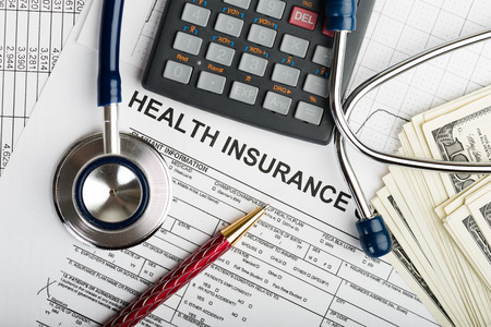 Health care costs. Stethoscope and calculator symbol for health care costs or medical insurance photo