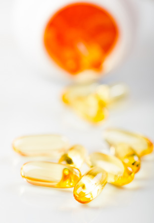 shiny yellow vitamin e fish oil capsule  spilling out of pill bottle photo