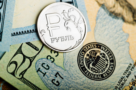 roubles: russian roubles coins on banknotes of us dollars Stock Photo