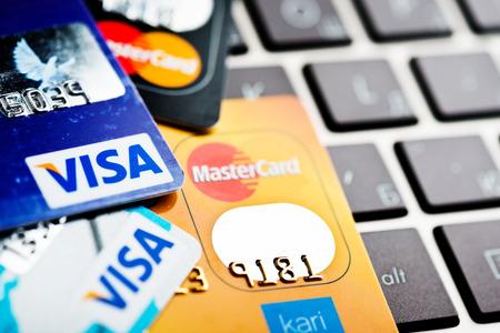 tarjeta visa: YEKATAERINBURG, Rusia - 07 de enero 2015: El hacer compras en Internet - tarjeta Visa y Mastercard en el teclado port�til.