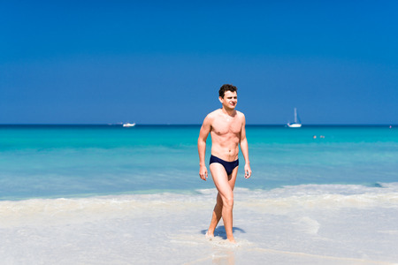Young handsome  man walking out of the water in a tropical beach photo