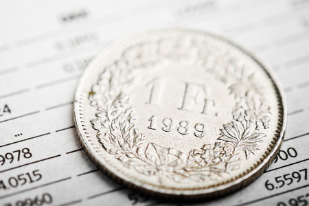 swiss franc: One Swiss Franc coin on fluctuating graph. Rate of the Swiss Franc (shallow DOF)