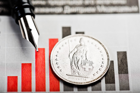 fluctuate: One Swiss Franc coin on fluctuating graph. Rate of the Swiss Franc (shallow DOF)