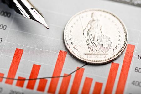 frank szwajcarski: Jeden frank szwajcarski monety na falujący wykresie. Kursy franka szwajcarskiego (płytkie DOF) Zdjęcie Seryjne