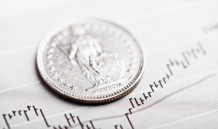 helvetia: One Swiss Franc coin on fluctuating graph. Rate of the Swiss Franc (shallow DOF)