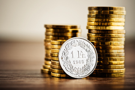 frank: one swiss frank coin and gold money on the desk Stock Photo