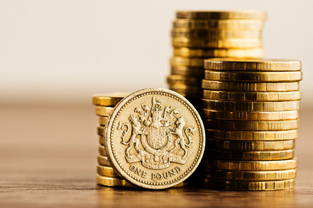 sterling: pound GBP moneta e monete d'oro sulla scrivania Archivio Fotografico