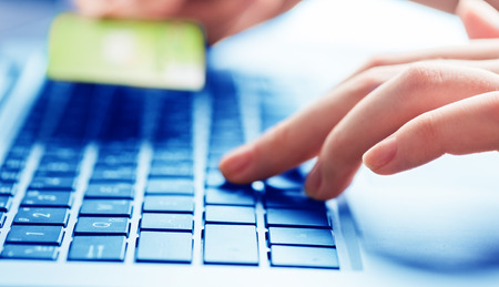 Hands holding a credit card and using laptop computer for online shopping photo