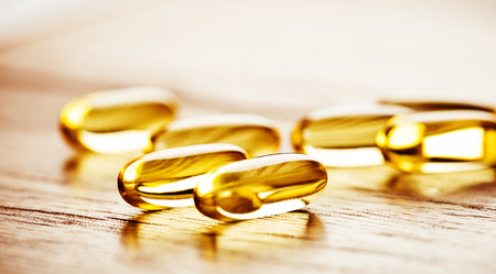 Fish oil omega 3 gel capsules  on wooden background