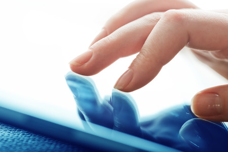 closeup of finger touching screen on tablet-pc photo
