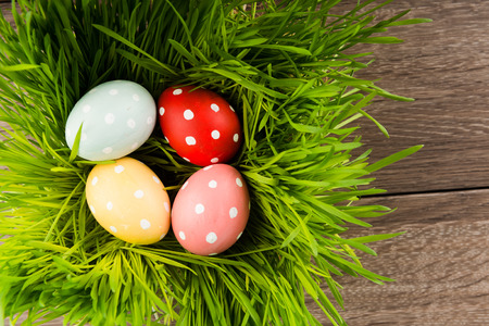 Easter eggs on green grass on wooden table photo