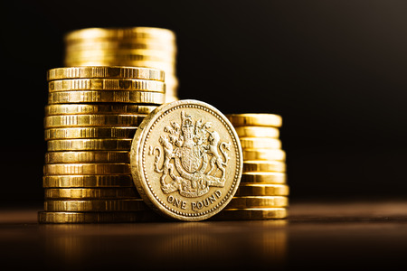pile of coins: pound GBP coin and gold money on the desk