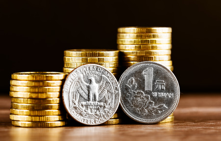 us coin: Chinese One Yuan Coin and us quarter dollar coin and gold money on the desk Stock Photo