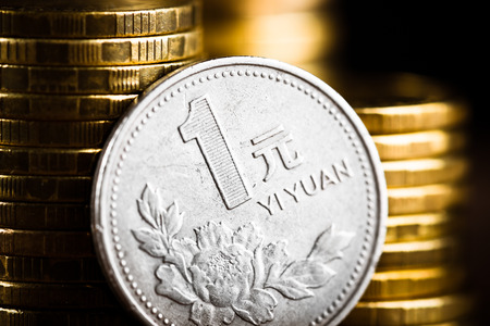 Chinese One Yuan Coin  and gold money on the desk. Peony flower depicted in the Chinese one Yuan coin. photo