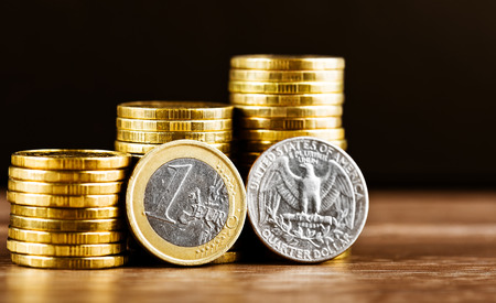 one euro coin and us quarter dollar coin and gold money on the desk photo