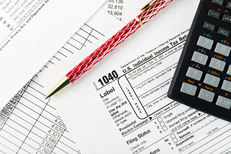 tax return: income tax return with pen and calculator Stock Photo