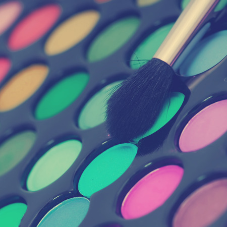 eye shadows: multicolored eye shadows with cosmetics brush.