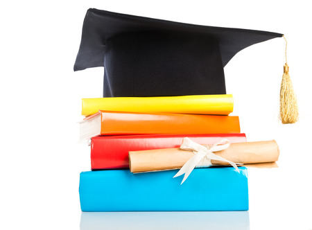 mortarboard: mortarboard and vintage graduation scroll, tied with red ribbon, on a stack of books