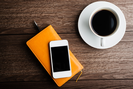 wood working: organizer with cup of coffee and mobile phone on desk Stock Photo