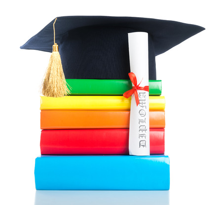 rewarded: A mortarboard and graduation scroll, tied with red ribbon, on a stack of books Stock Photo