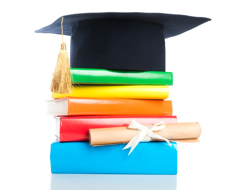 rewarded: mortarboard and vintage graduation scroll, tied with red ribbon, on a stack of books