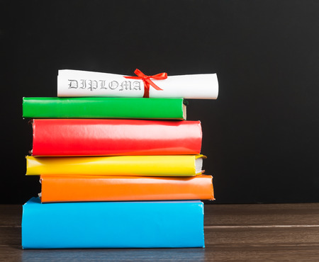 baccalaureate: Stack Of Text Books And Graduation Scroll Stock Photo