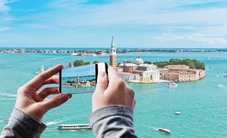 Tourist taking a picture of San Giorgio island in Venice, Italy photo
