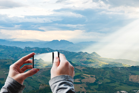 Tourist taking a picture of Sun rays shining down on hills in San Marino photo