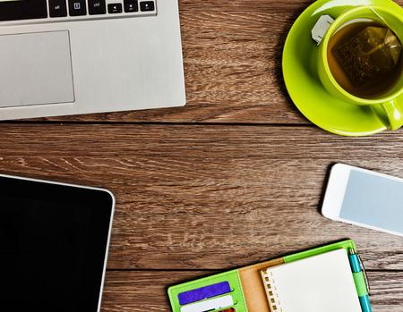 Büro-Schreibtisch mit Laptop-Computer, Tablet-PC, Planer, Stift, mobile Smartphone und eine Tasse Tee. Standard-Bild