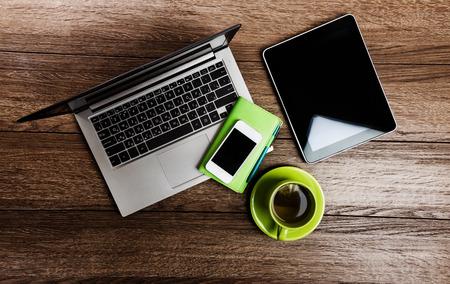 Scrivania con computer portatile, tablet pc, pianificatore, penna, smartphone mobili e tazza di tè.