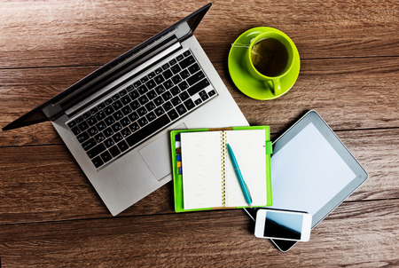 Office desk with laptop computer, tablet pc, planner, pen, mobile smartphone and cup of tea. Stockfoto
