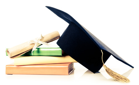 mortarboard and vintage graduation scroll, tied with red ribbon, on a stack of books