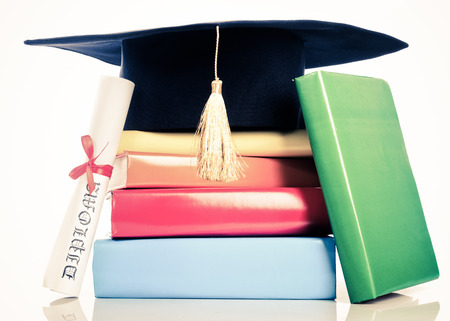 mortarboard: A mortarboard and graduation scroll, tied with red ribbon, on a stack of books Stock Photo